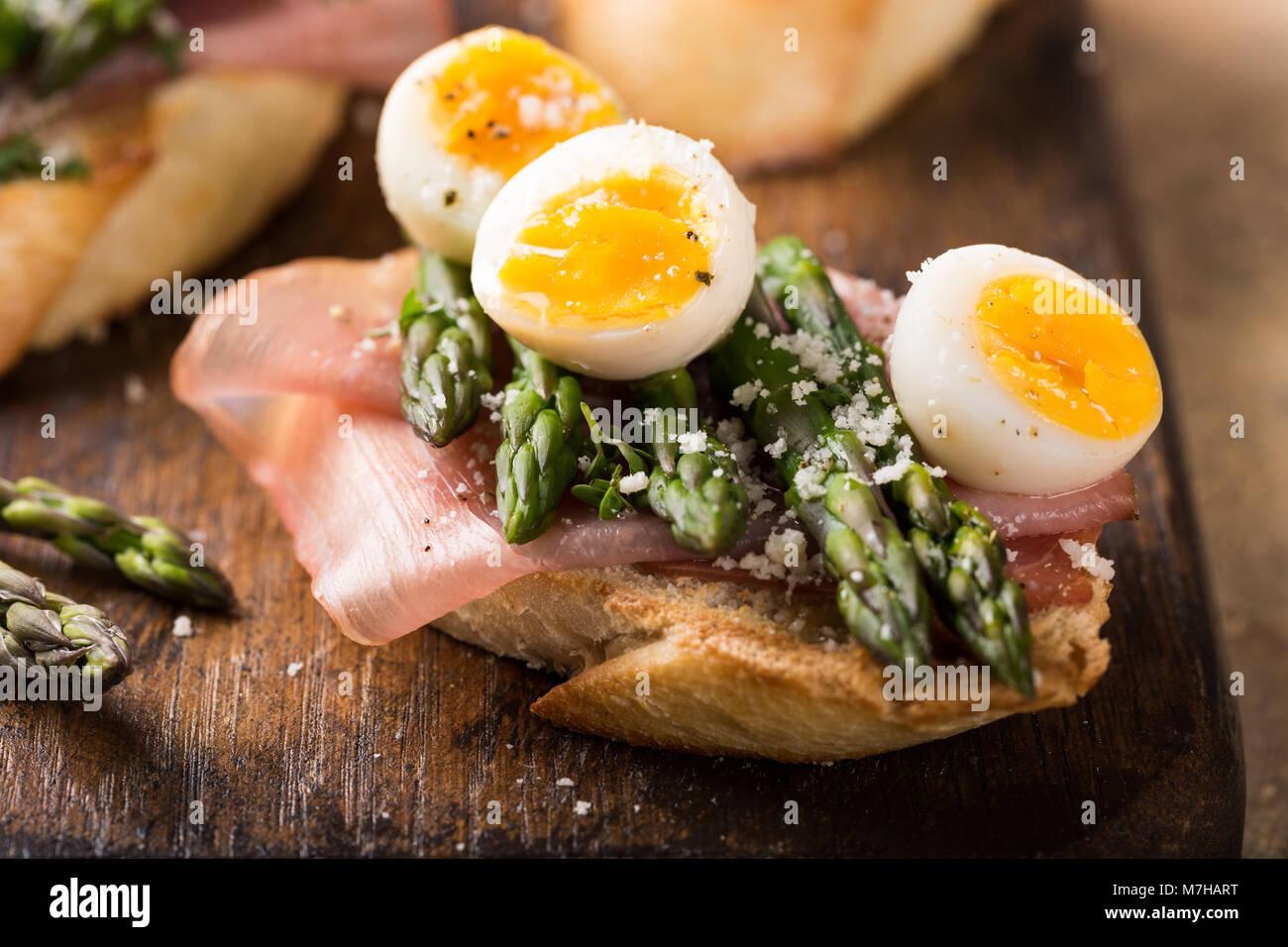 Fresh sendwich with ham, asparagus and quail eggs - Stock Image