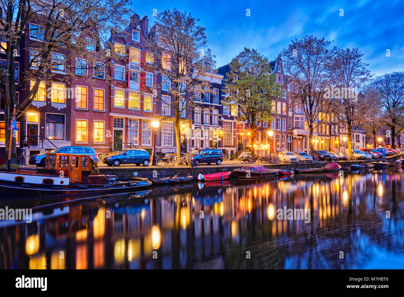 Amterdam canal, boats and medieval houses in the evening - Stock Image