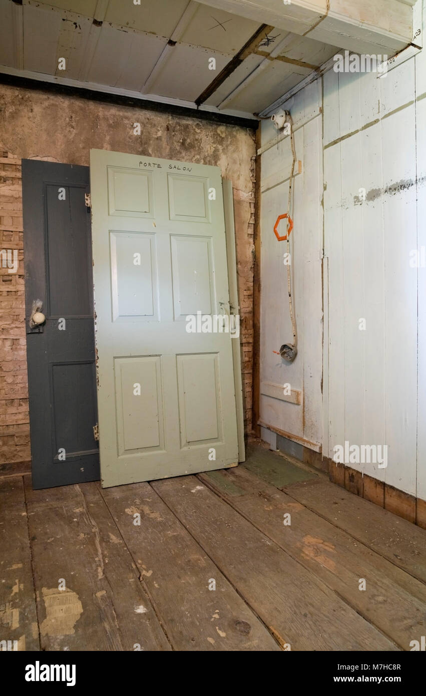Stacked wooden doors and partially demolished plaster and wooden wall in a empty room inside an old 1800s cottage Stock Photo