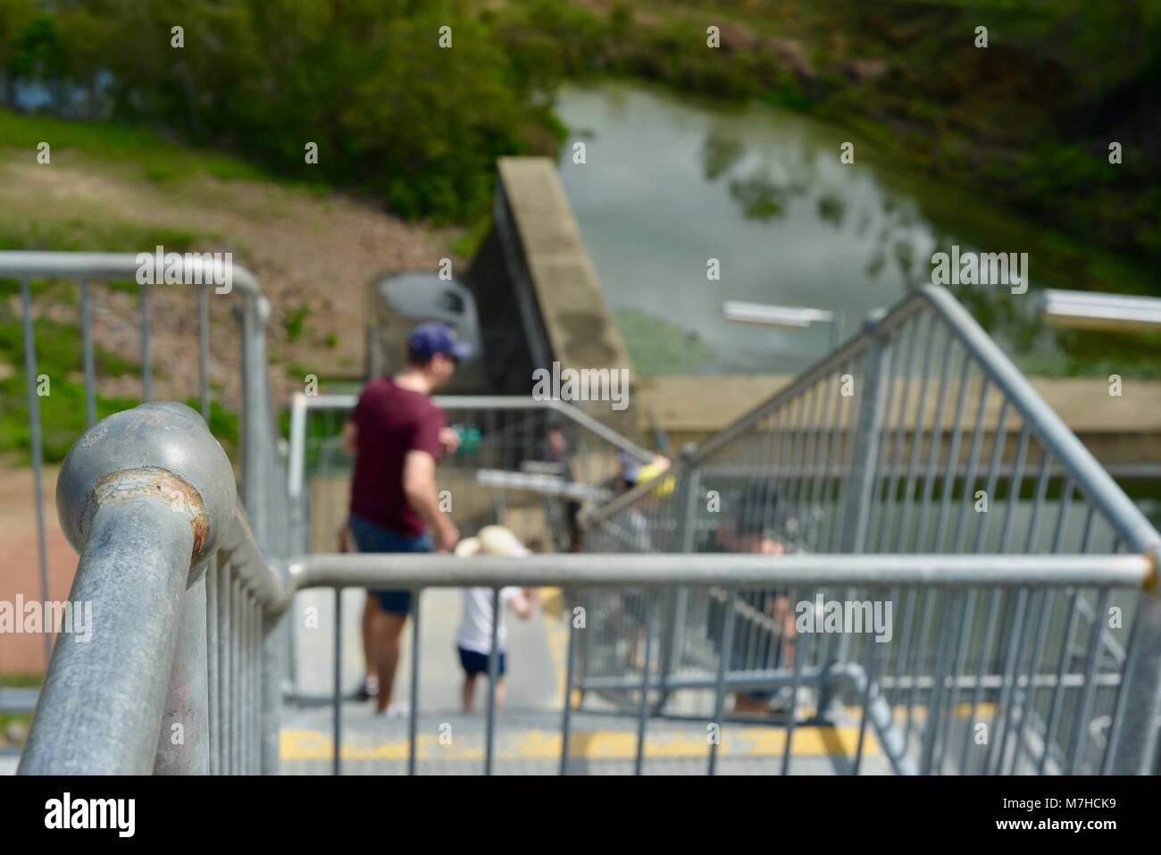 Father and son walking down galvanised steel stairs, Ross River Dam, Ross Dam Access, Kelso QLD, Australia - Stock Image