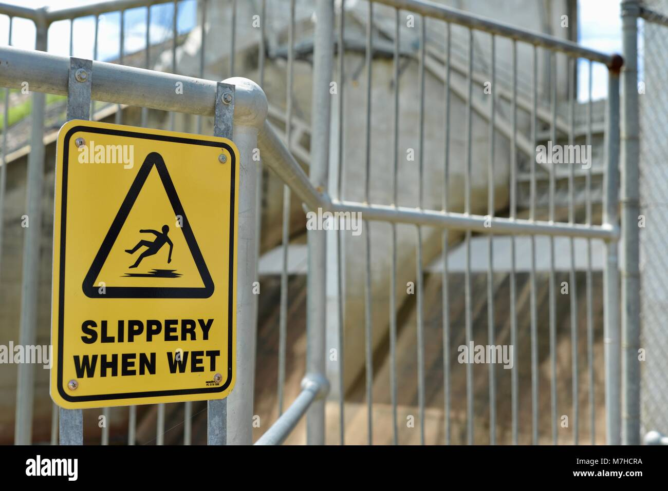 slippery when wet sign with image of man falling over, Ross River Dam, Ross Dam Access, Kelso QLD, Australia - Stock Image