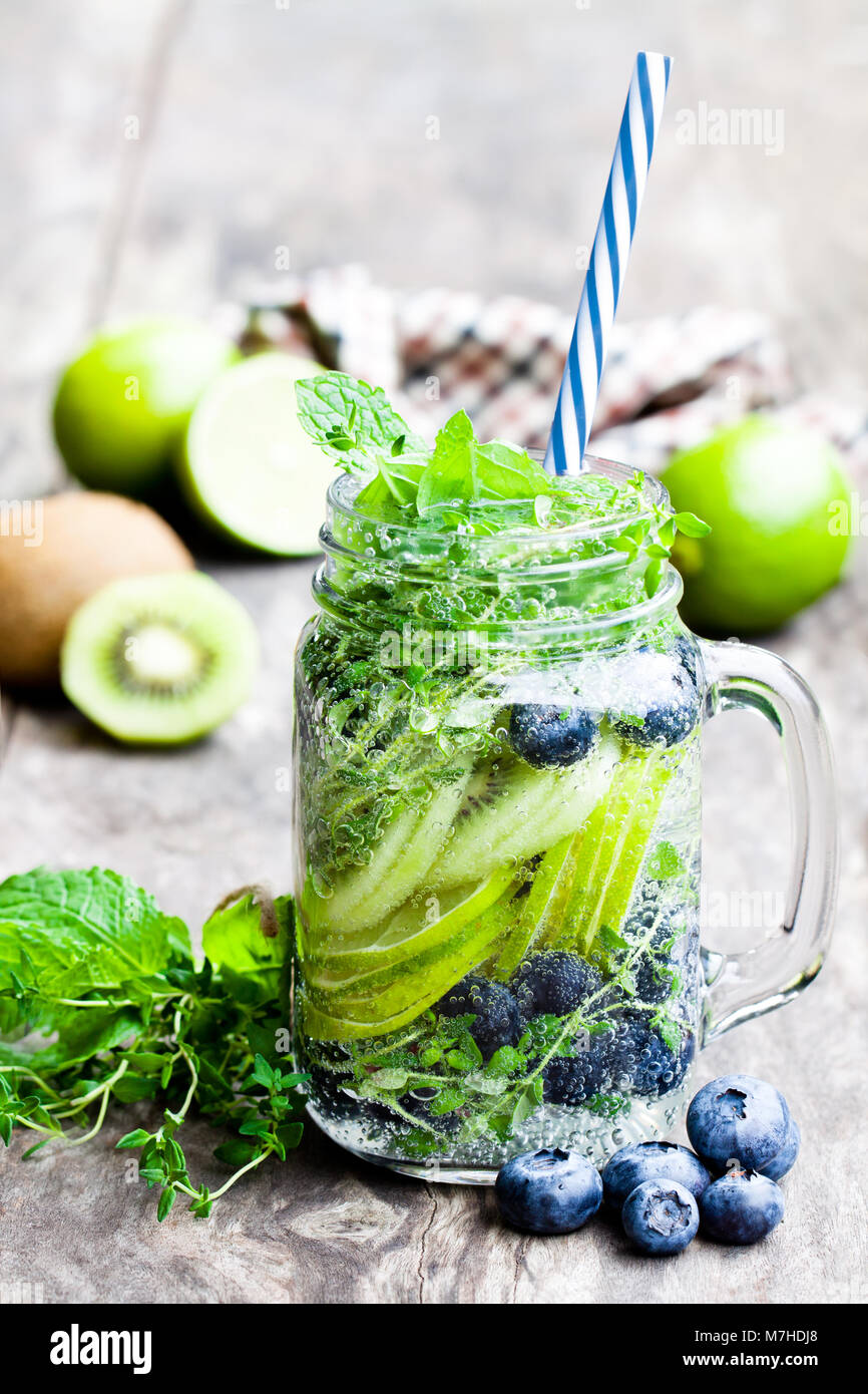 Detox  water. Homemade summer fruit drink with lime and kiwi and blueberry - Stock Image