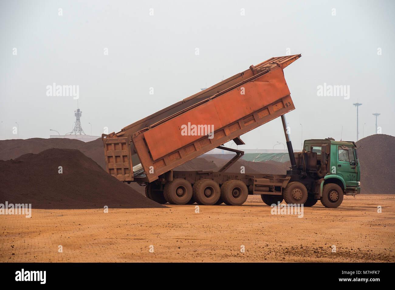 Iron Ore stockpile storage on the docks in Tianjin Port China. - Stock Image