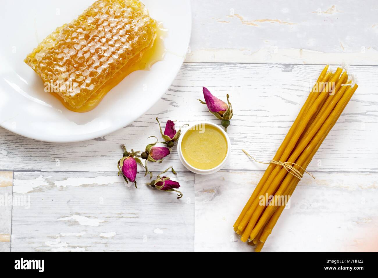 organic honeycomb, honey lip balm and natural wax candles on wooden white background Stock Photo