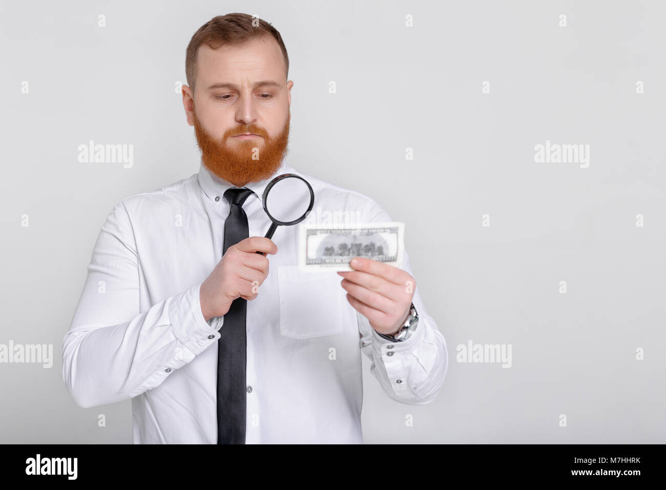 expert looking at magnifying glass for bill Stock Photo