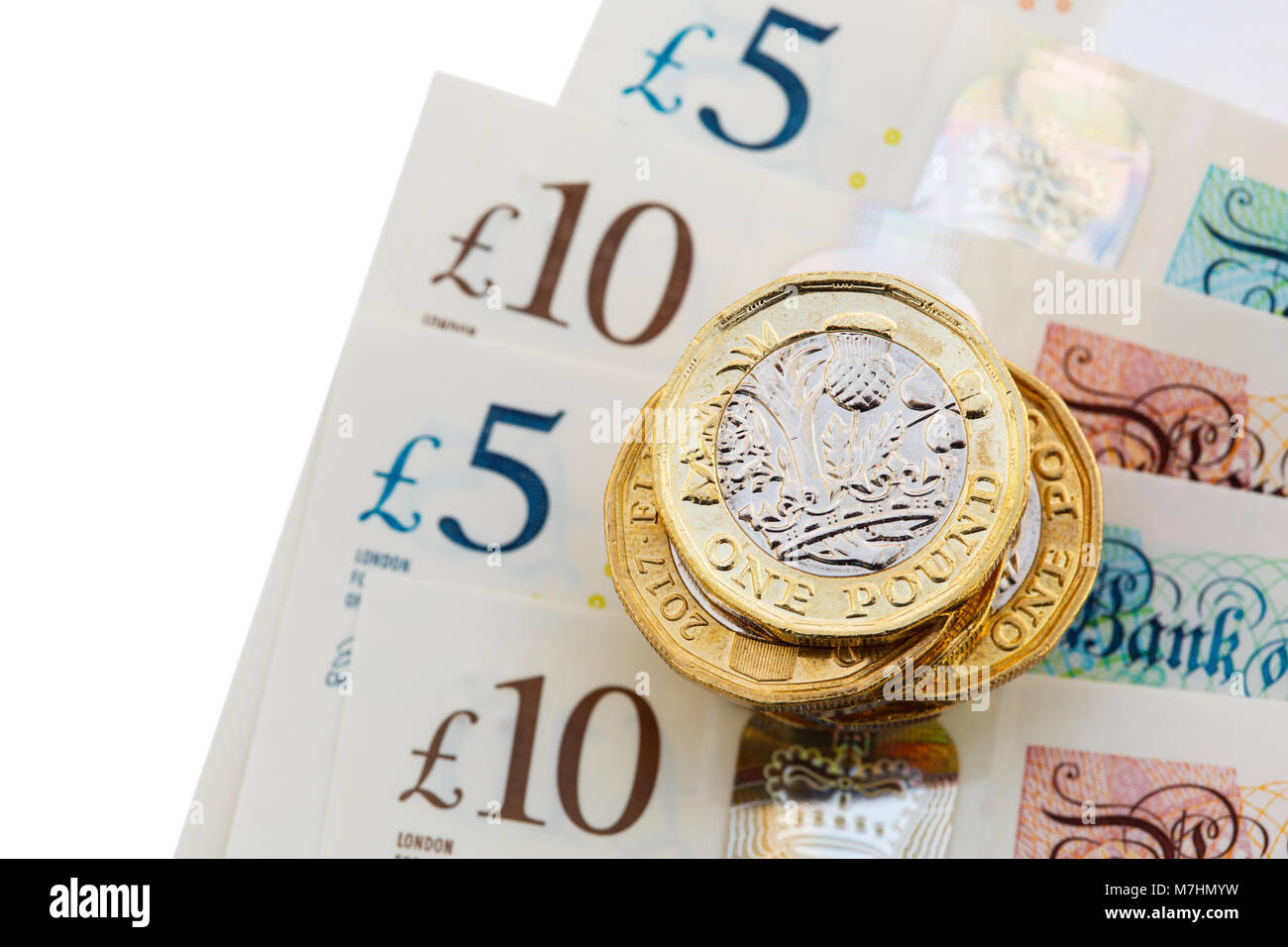 Pile of new 12-sided English one pound coins £ pounds sterling money cash on new polymer plastic £10 and £5 notes Stock Photo