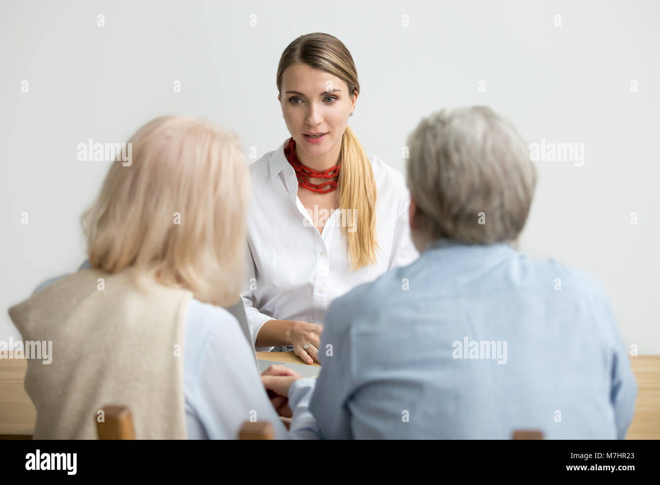 Female financial advisor talking consulting senior aged couple a - Stock Image