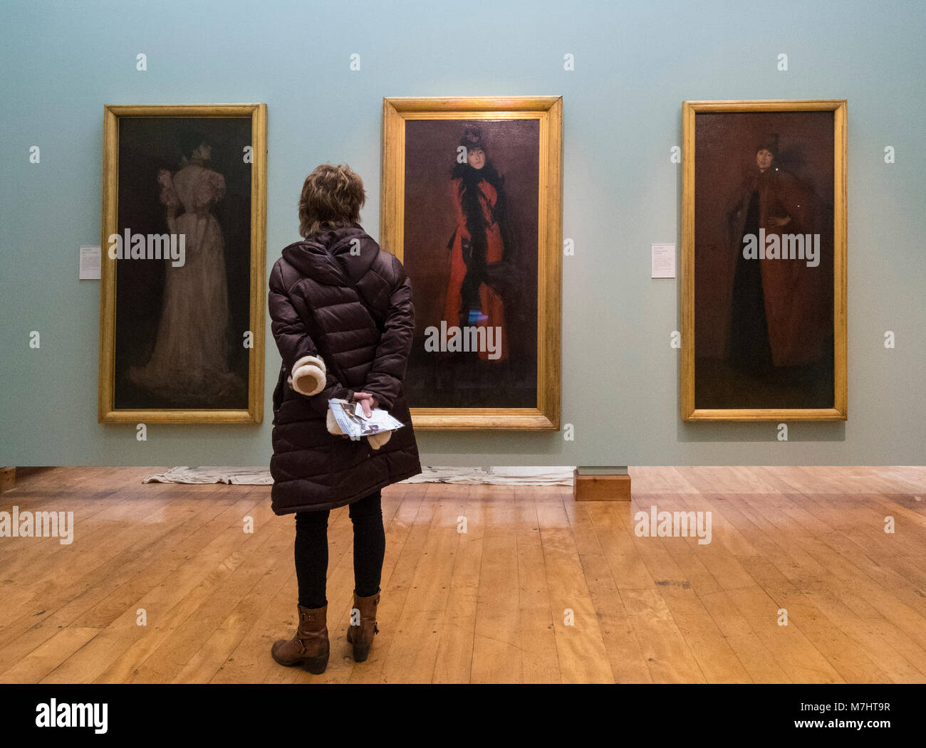 Visitor to Hunterian Art Gallery looking at paintings by James Abbott McNeill Whistler at Glasgow University, Scotland, - Stock Image