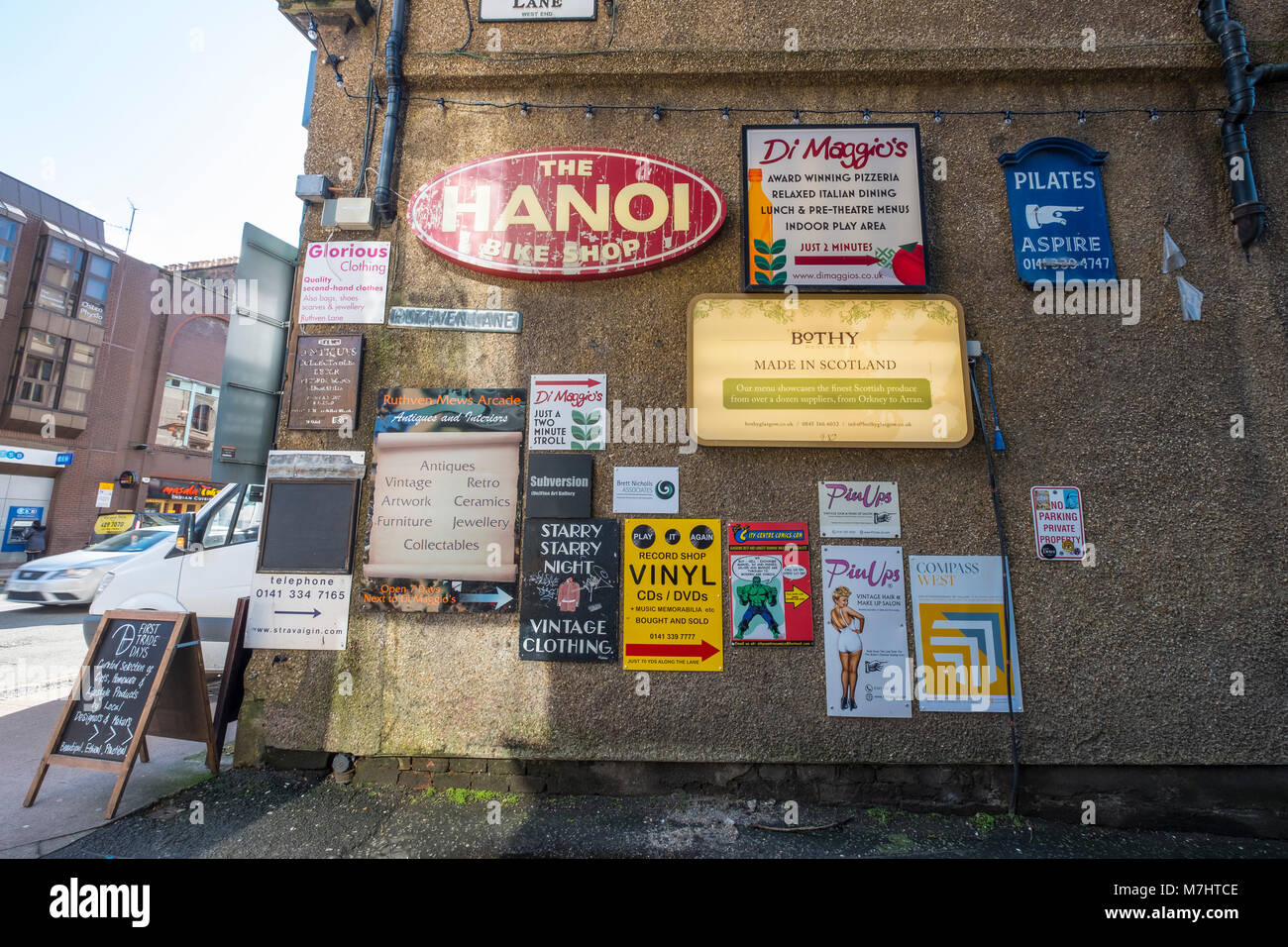 Entrance to Ruthven Lane mews with many shop and restaurant sign boards off Byres Road in Glasgow West End, Scotland, - Stock Image