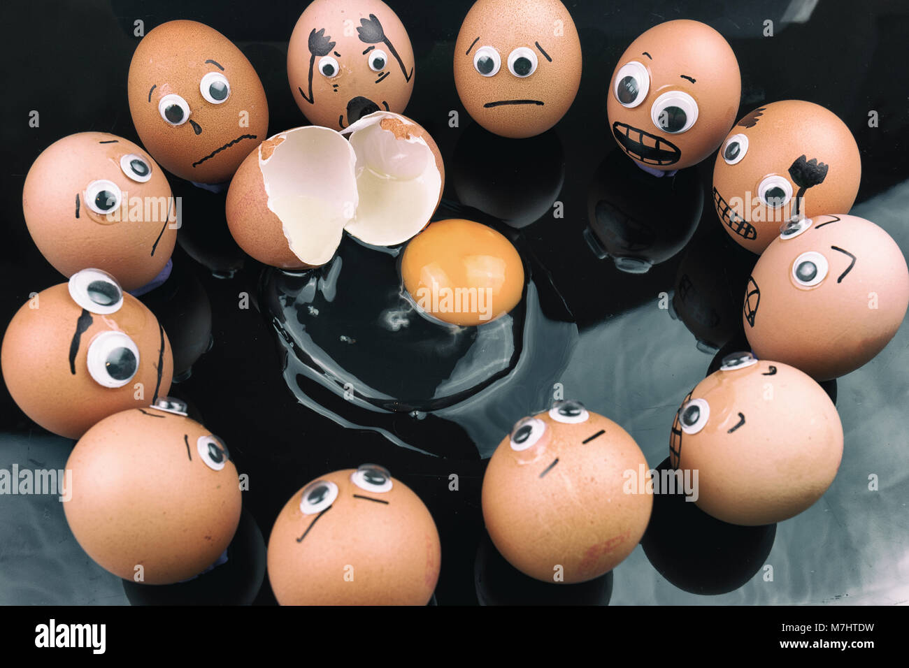 Fun concept: raw eggs with googly eyes and drawn features are in shock and sad as they witness another egg broken - Stock Image