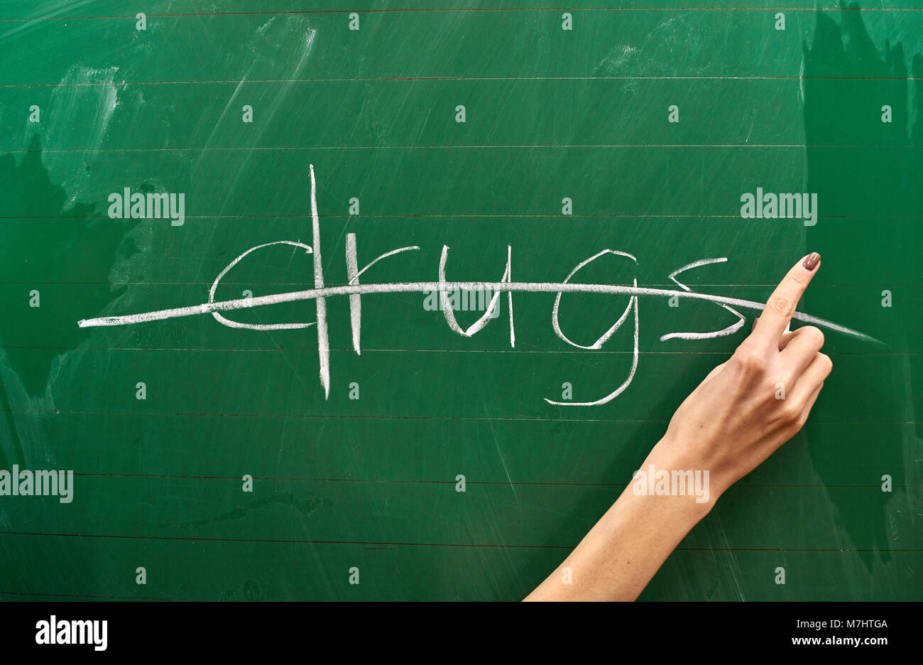 Right hand of a teenage girl writing drug protest on the green school board background - Stock Image