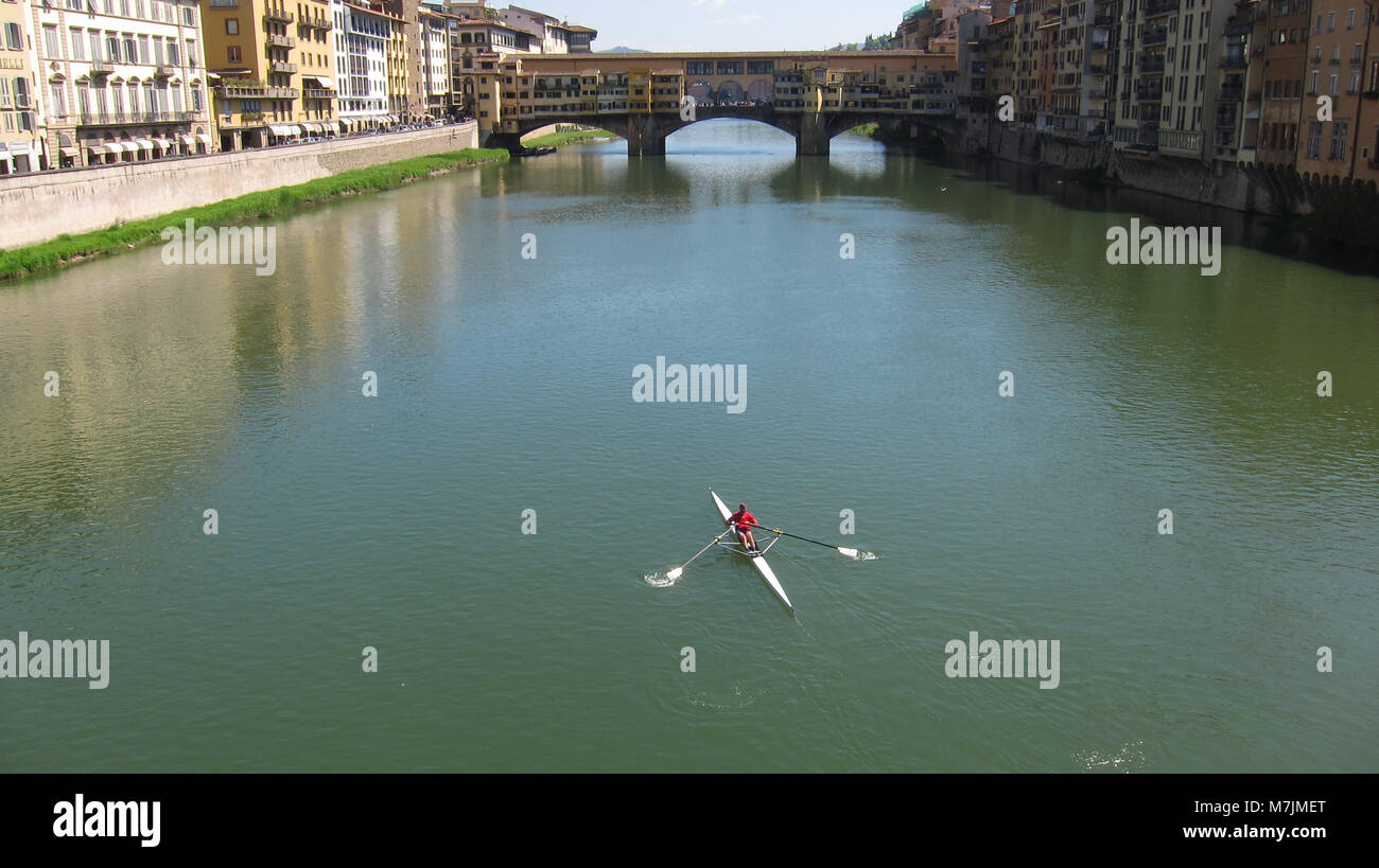 Man Skulls Alone on the River Arno in a Bright Red Shirt on a Sunny Afternoon in Florence - Stock Image