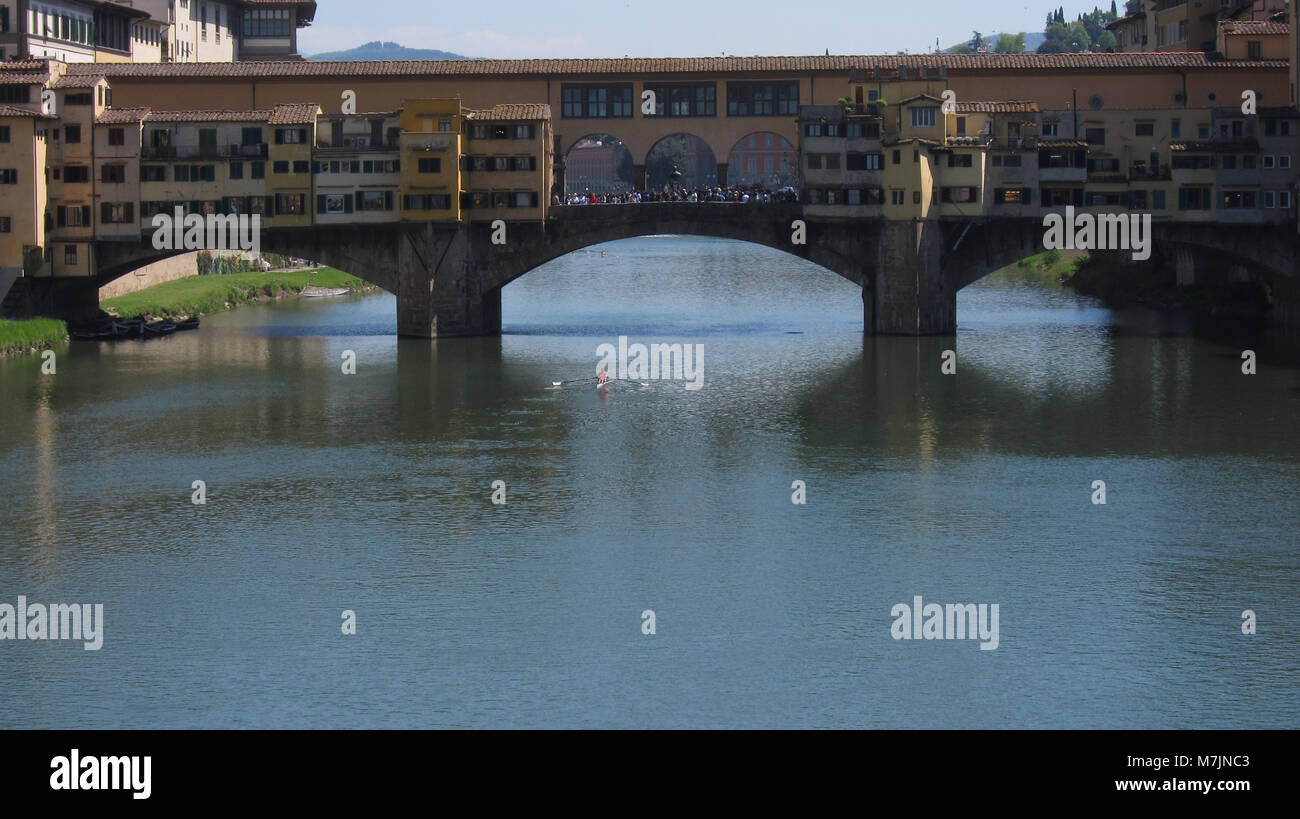 Skulling Under Il Ponte Vecchio on the Arno River, Florence, Italy - Stock Image