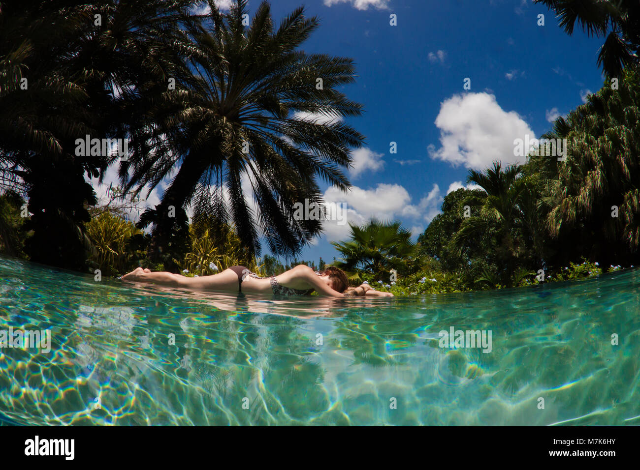A woman lies at the edge of an infinity pool with a tropical background on the island of Curacao, Netherlands Antilles, - Stock Image