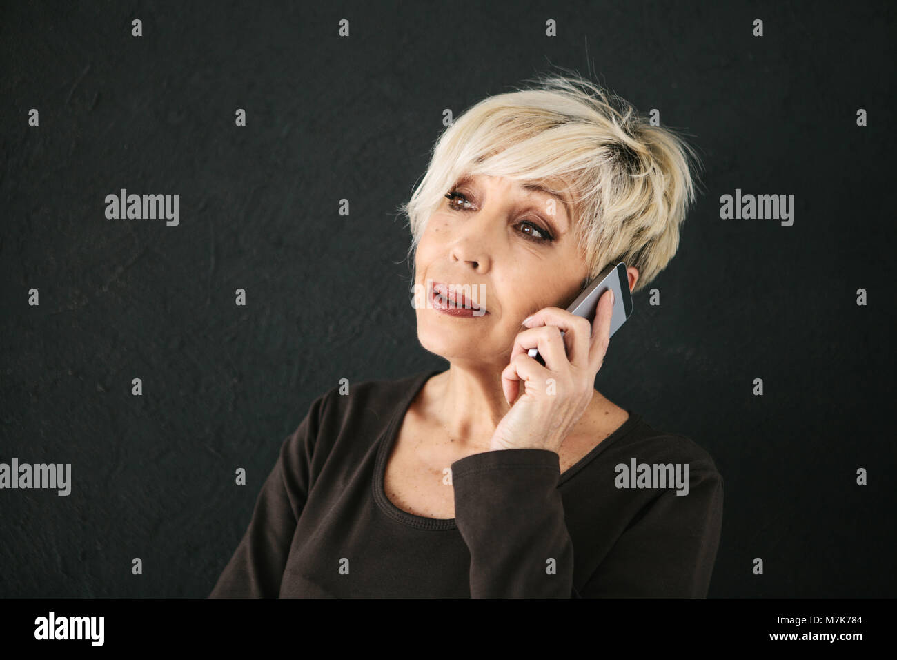 A successful positive elderly female consultant is negotiating a cell phone. Communication between people using - Stock Image