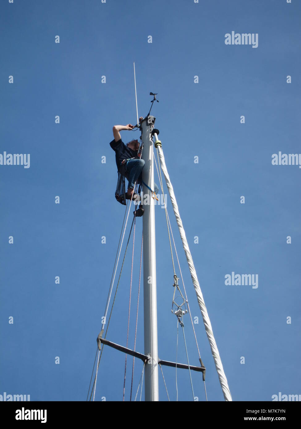 PLERIN,FRANCE-22MAY,2017: Sailor mounted on the mast of his boat in the port of Légué side Plérin - Stock Image
