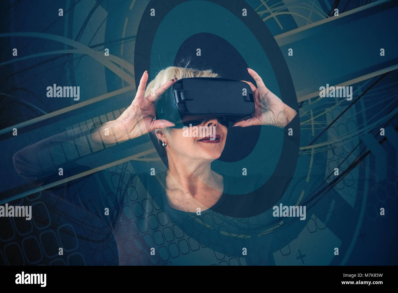 An elderly woman in virtual reality glasses. With visual effects. An elderly person using modern technology. - Stock Image