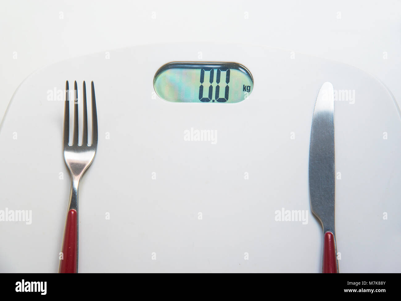 Fork and knife on a weight scale. - Stock Image