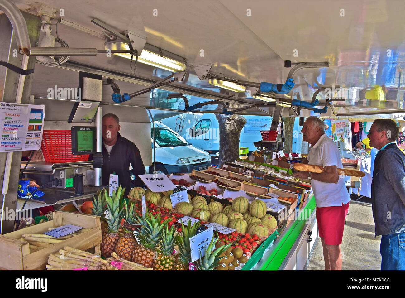 Frenchman at fruit stall in the local market at Bretignole sur Mer in the Vendée region of France. - Stock Image