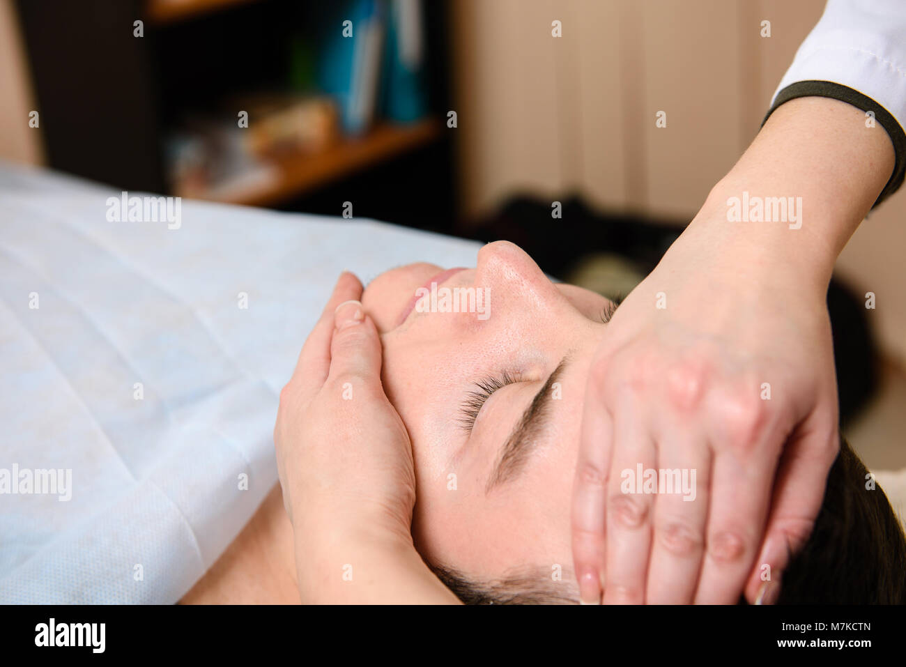 Doctor massages the face to the patient. Close-up of hands in beauty clinic. - Stock Image