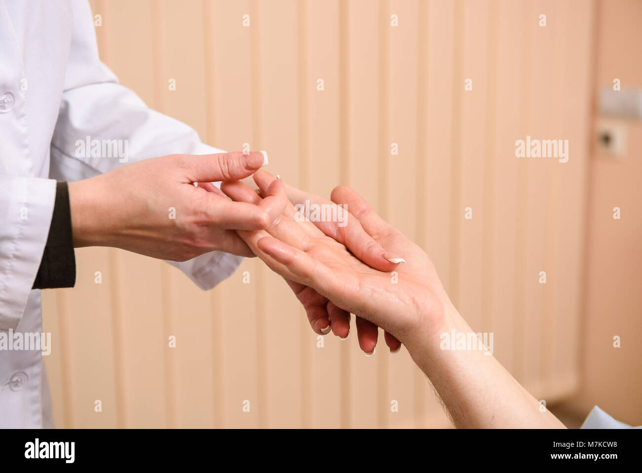 Close-up of hands in beauty clinic. Doctor massages an arm to the patient - Stock Image