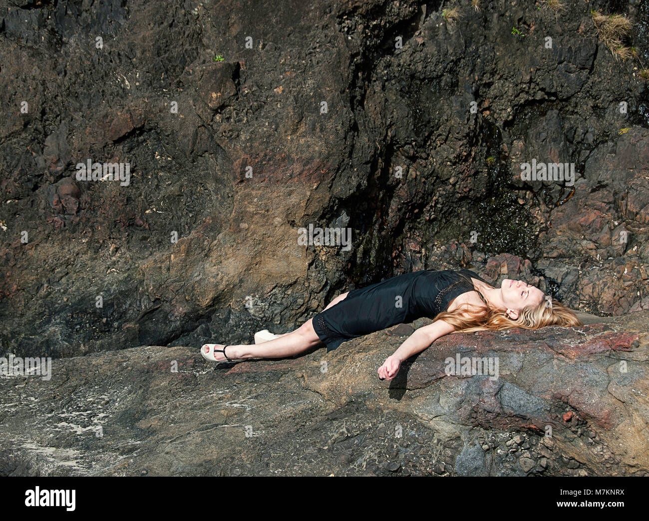A woman laying down on a coastal rock wearing high heels. - Stock Image