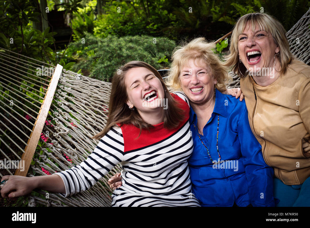 Three generations of women sitting in a hammock enjoying each others company. - Stock Image