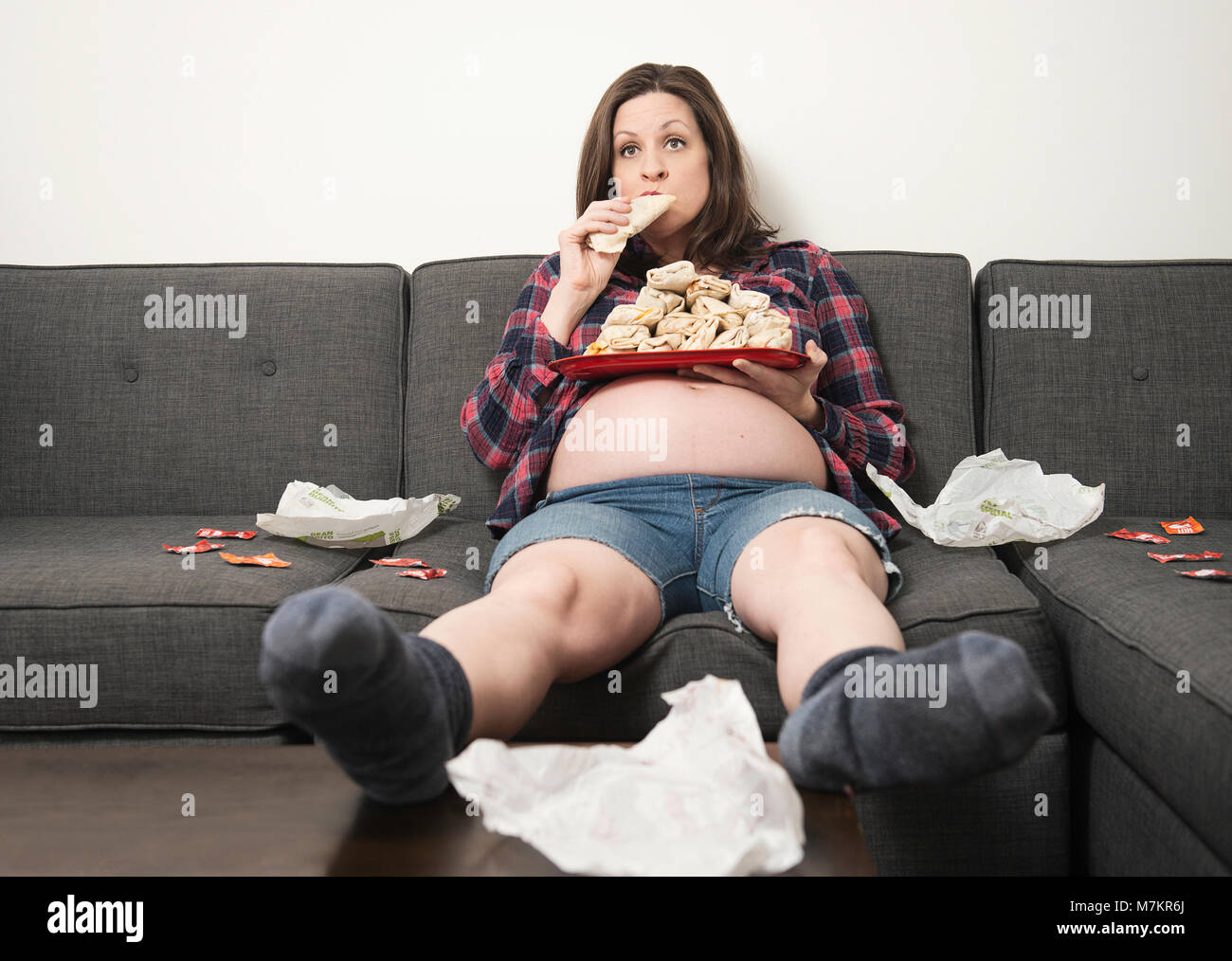 A woman satisfying her pregnancy cravings - Stock Image