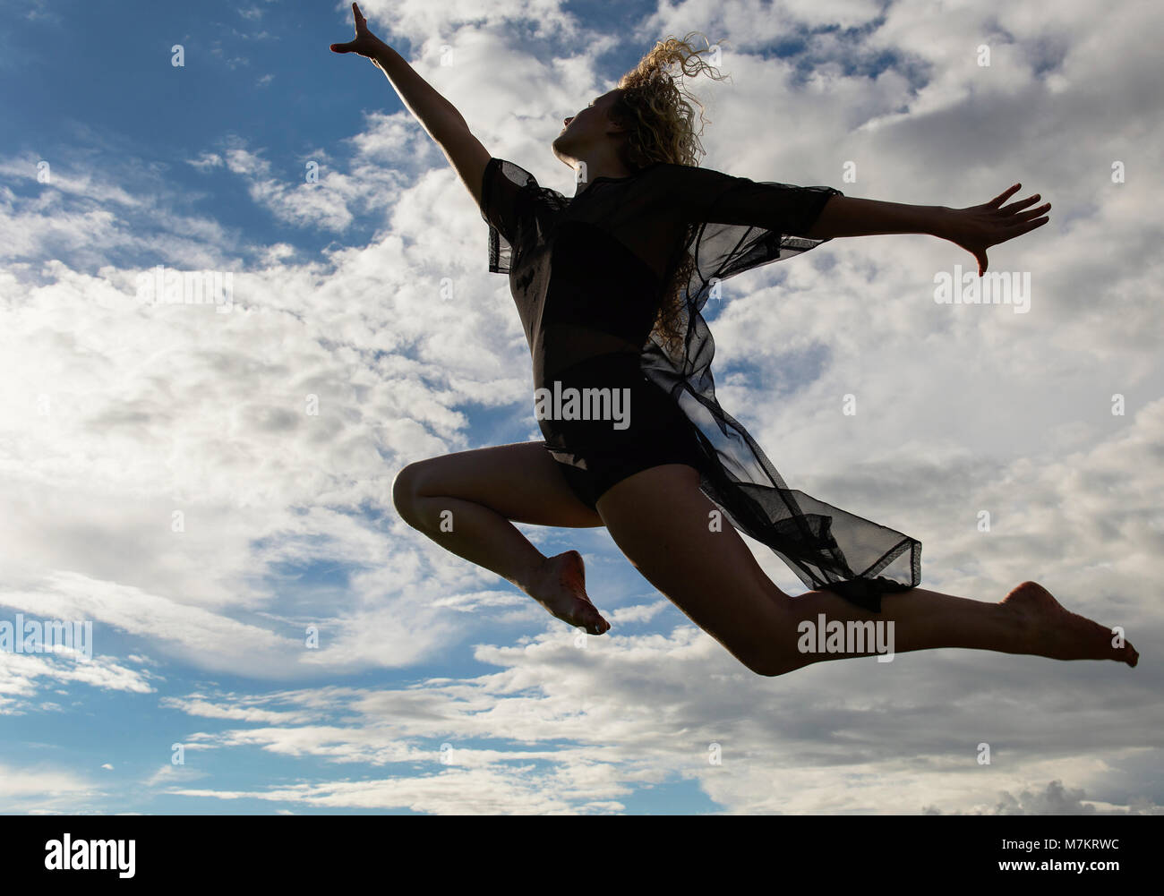 A young woman soaring in the sky - Stock Image