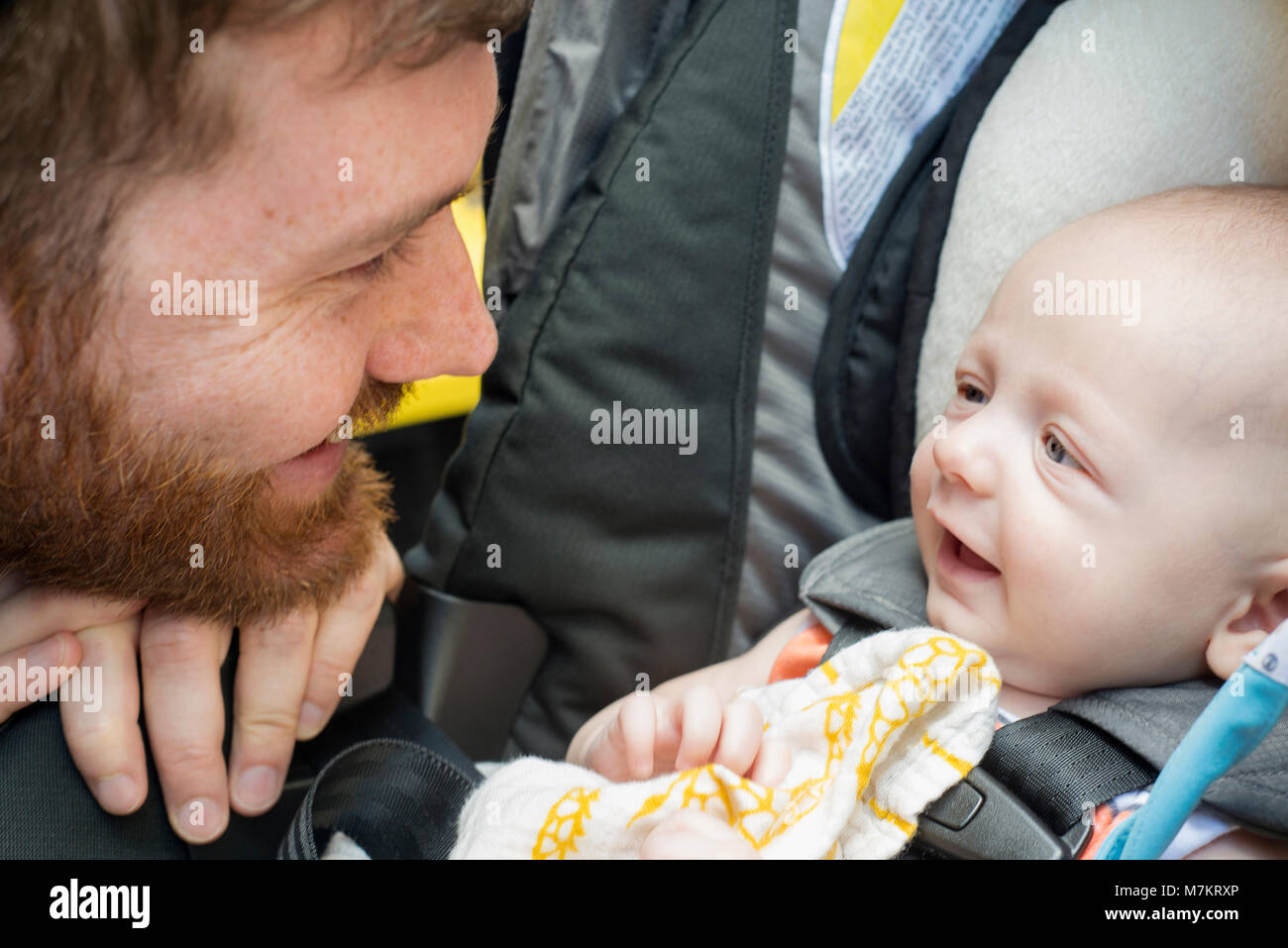 A man smiling at this infant son. 3 months old. - Stock Image