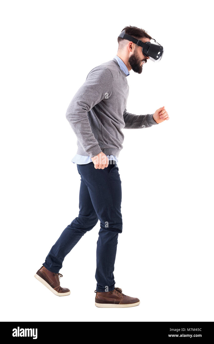 Side view of bearded man watching virtual reality glasses running and looking down. Full body isolated on white - Stock Image