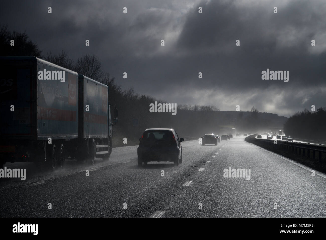 Spray from surface water on the M5 motorway creates poor visibility and dangerous driving conditions - Stock Image