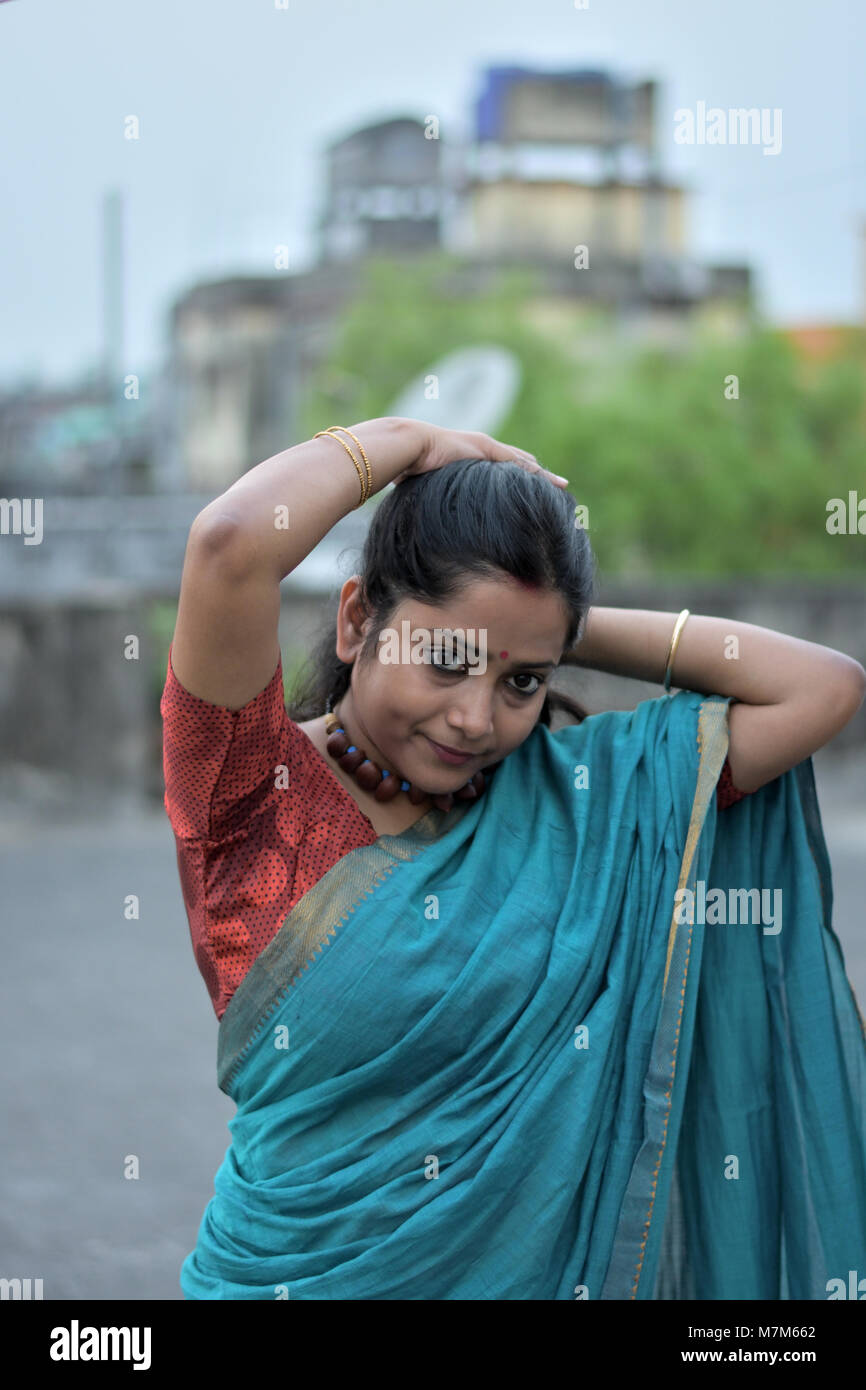 Young Bengali lady is tying her hair at rooftop - Stock Image