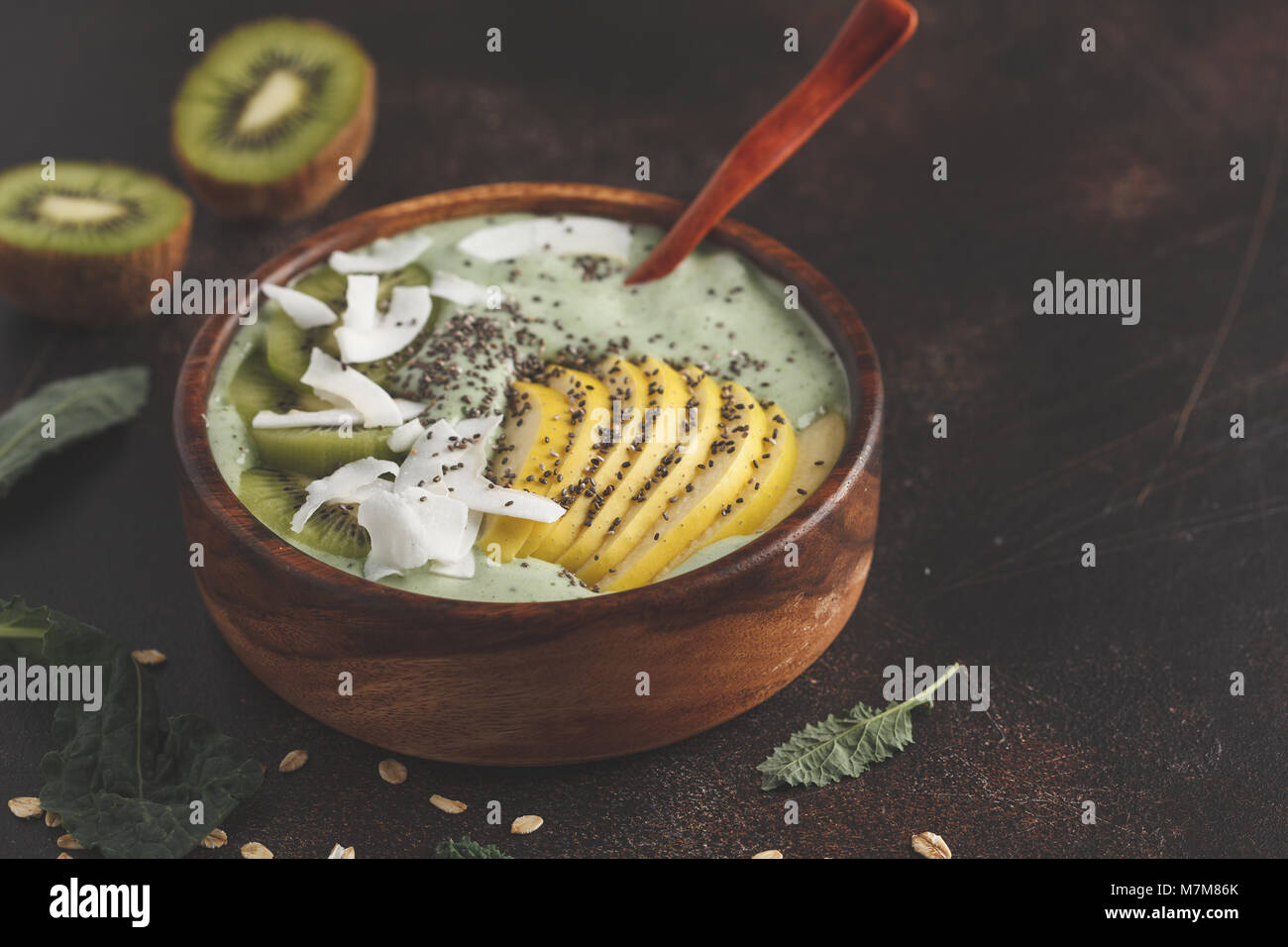 Green kale vegan smoothie bowl with coconut, chia, apple and kiwi. Healthy vegan food concept. Dark rusty background, - Stock Image