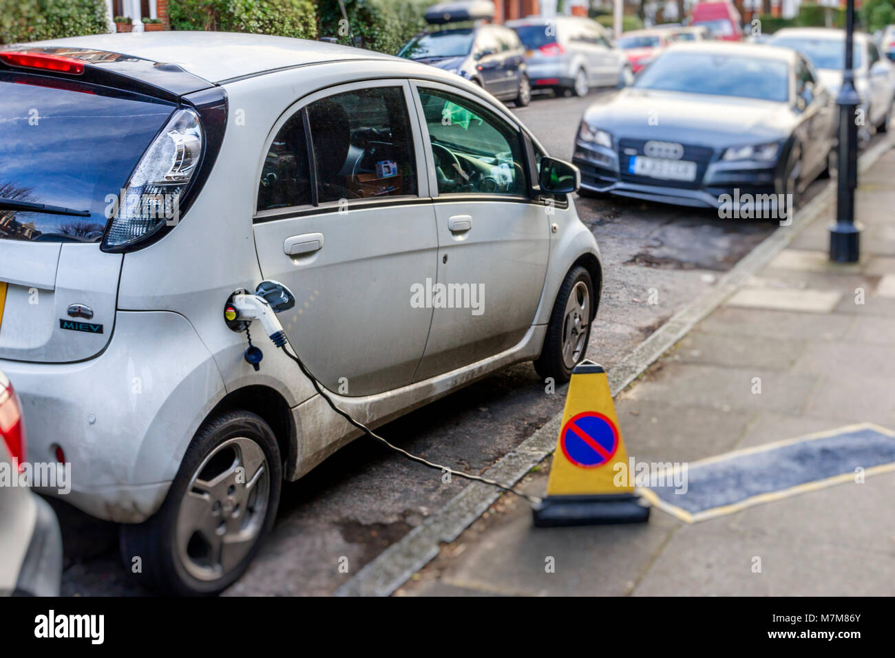 An electric-powered car being recharged at the kerbside in a residential street in North London, UK Stock Photo