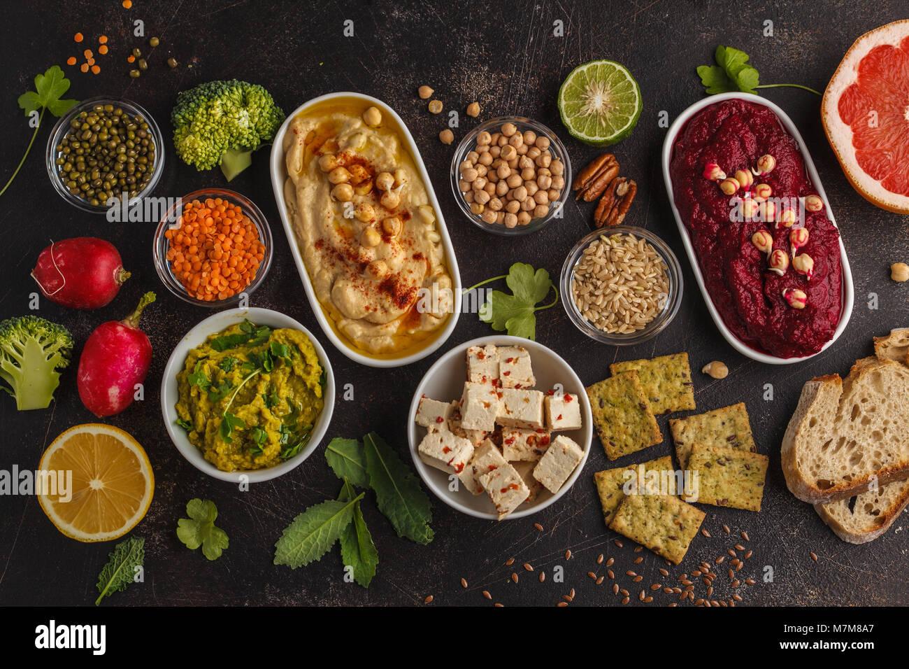 Vegan food background. Vegetarian snacks: hummus, beetroot hummus, green peas dip, vegetables, tofu. Top view, dark - Stock Image