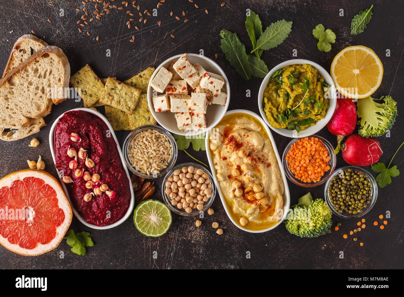 Vegan food background. Vegetarian snacks: hummus, beetroot hummus, green peas dip, vegetables, tofu. Top view, dark Stock Photo