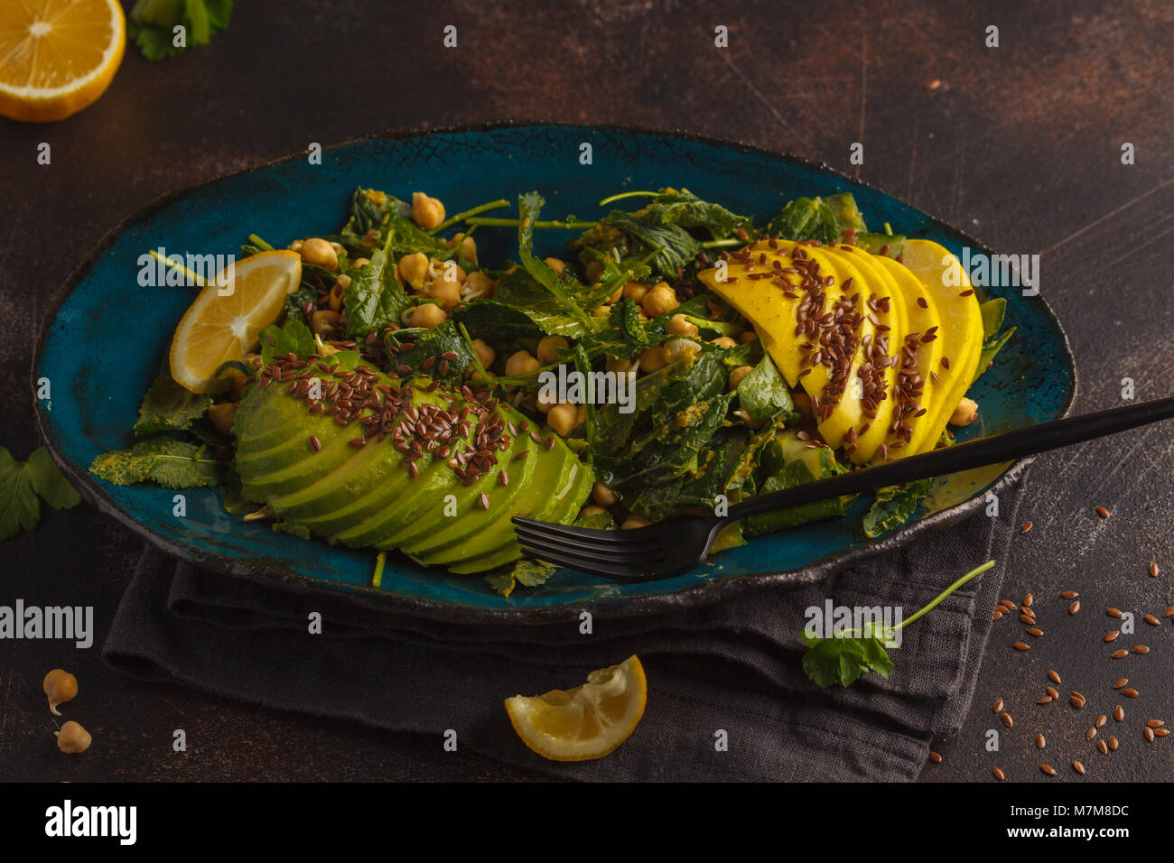 Healthy vegan avocado, chickpeas, kale salad in a vintage blue plate on a dark rusty background. Vegan food concept. - Stock Image