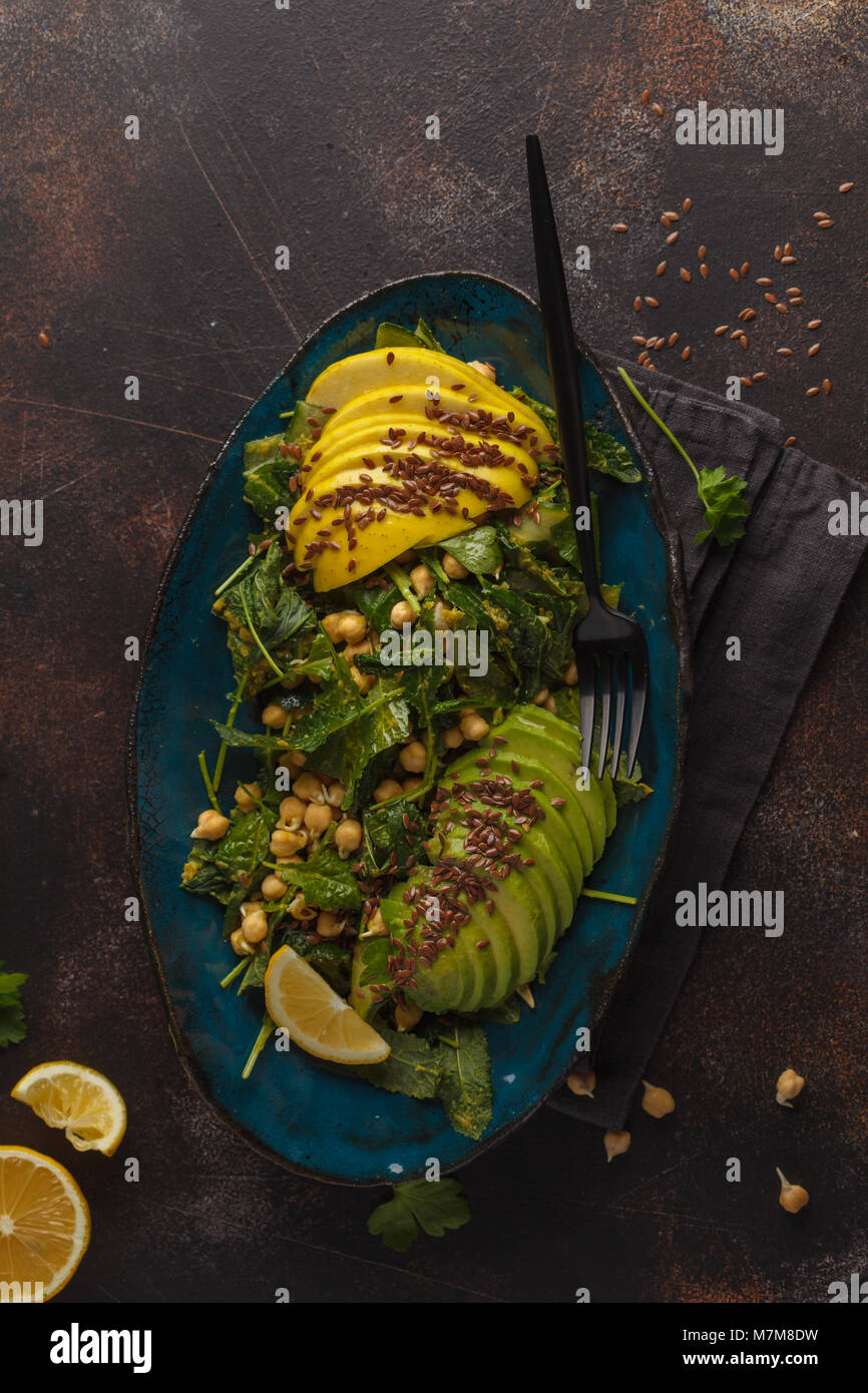 Healthy vegan avocado, chickpeas, kale salad in a vintage blue plate on a dark rusty background. Vegan food concept. Stock Photo