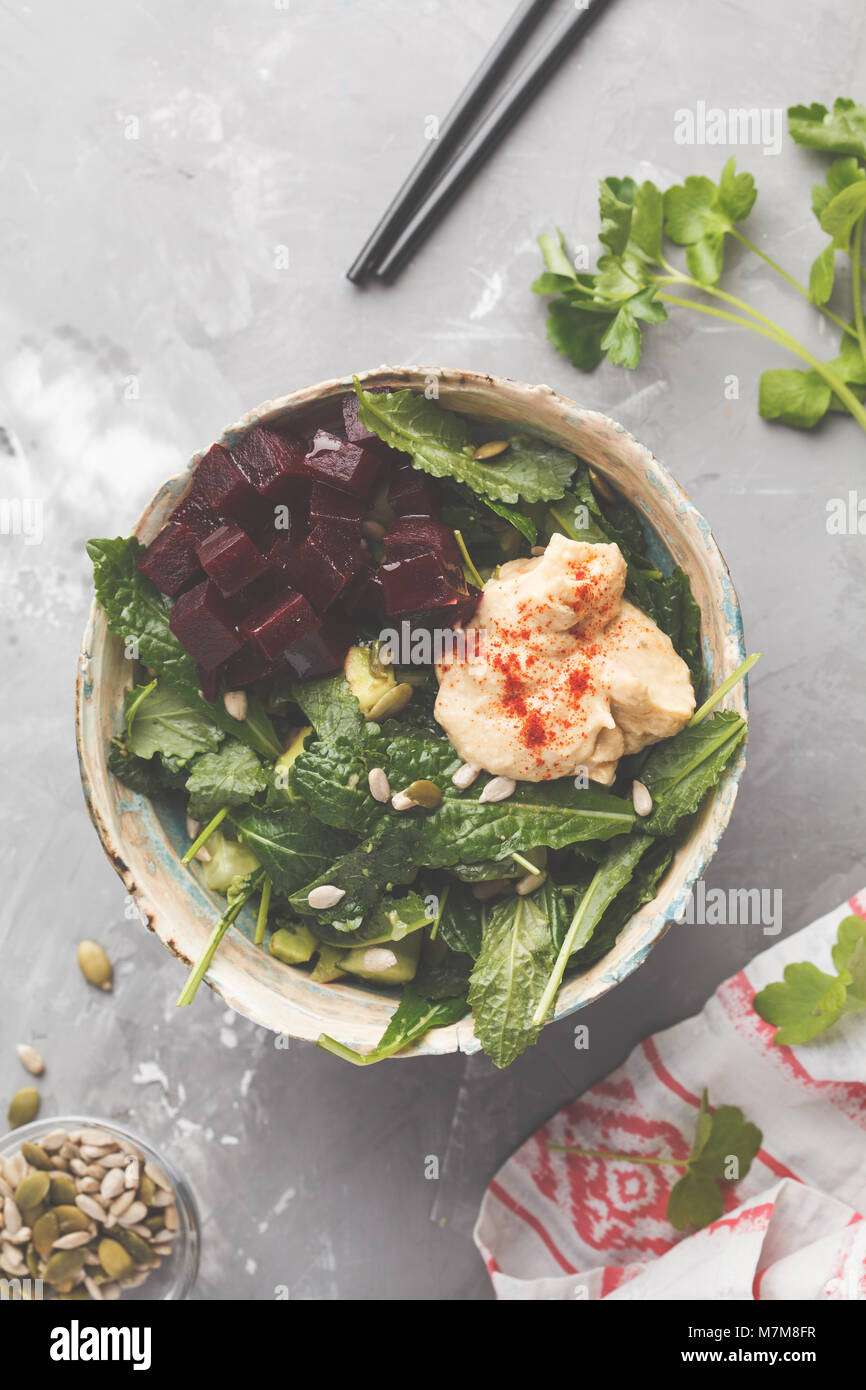 Green vegan salad with kale, beetroot, cucumber, sunflower seeds with hummus dressing. Healthy vegetarian food concept. - Stock Image