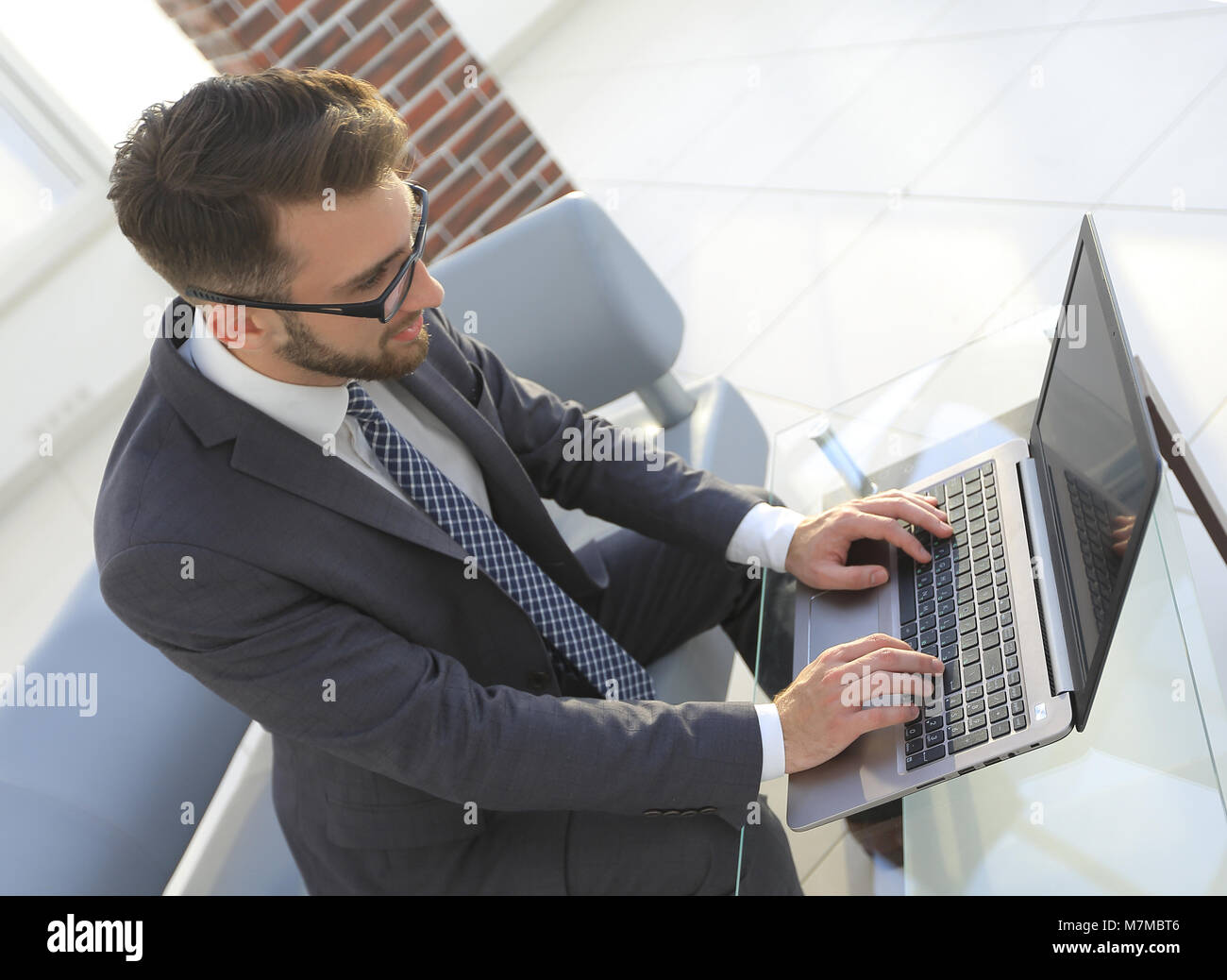 Concentrated professional IT developer with laptop - Stock Image