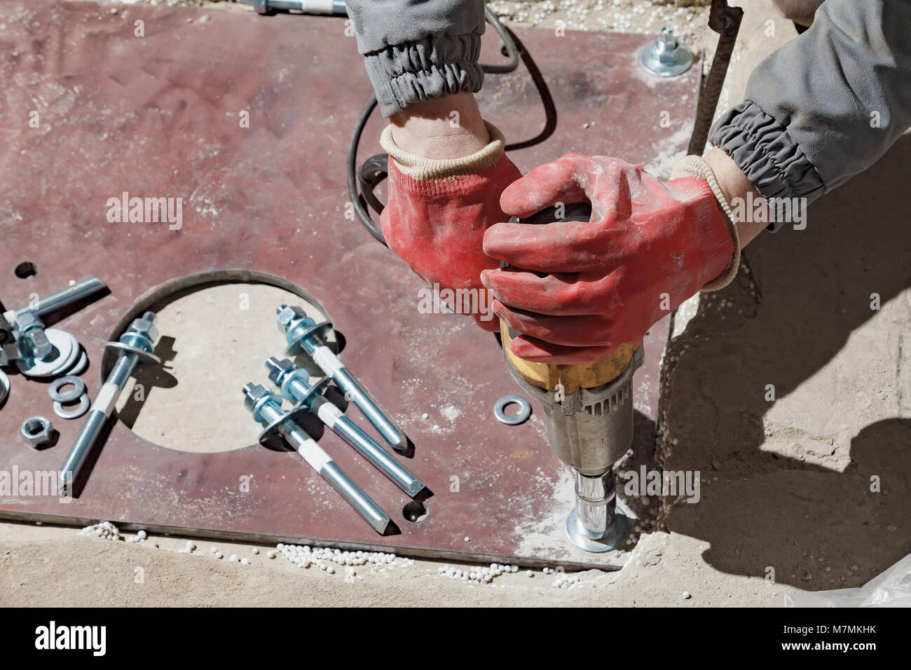 The builder rotates the nuts with an electric key. Screwing the bolts in the metal plate - Stock Image
