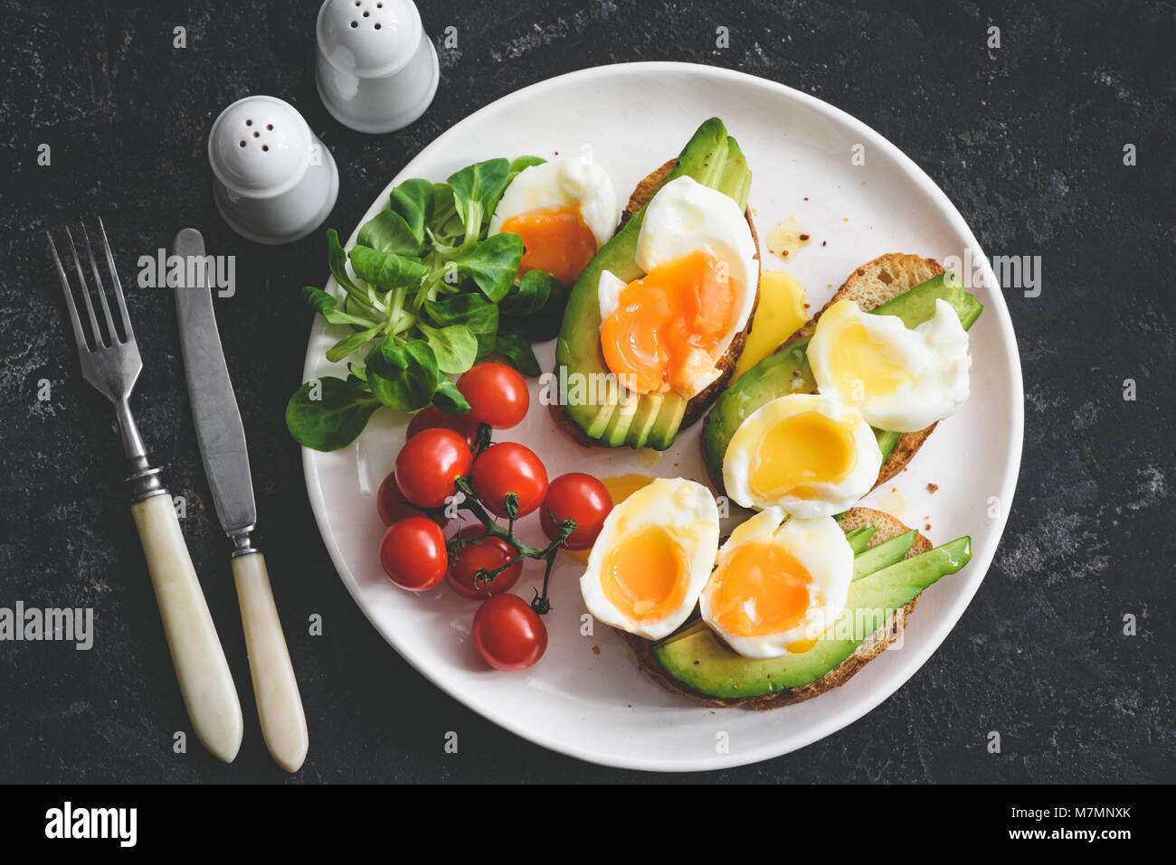 Poached egg and avocado toasts on white plate, top view, toned image. Healthy breakfast or lunch - Stock Image