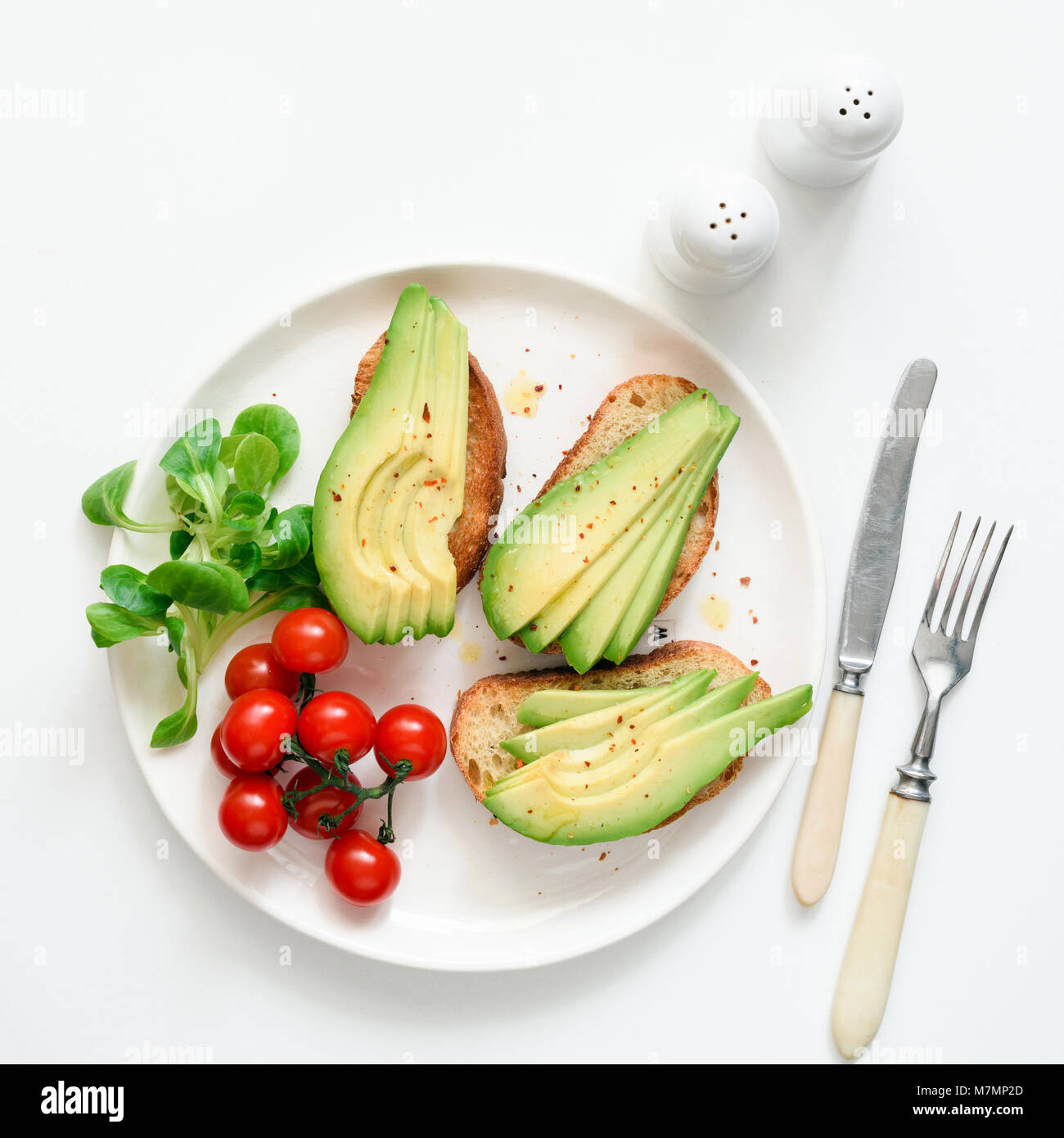 Avocado toasts, cherry tomatoes and salad on white plate, top view, square crop. Healthy lifestyle, vegen, vegetarian, Stock Photo