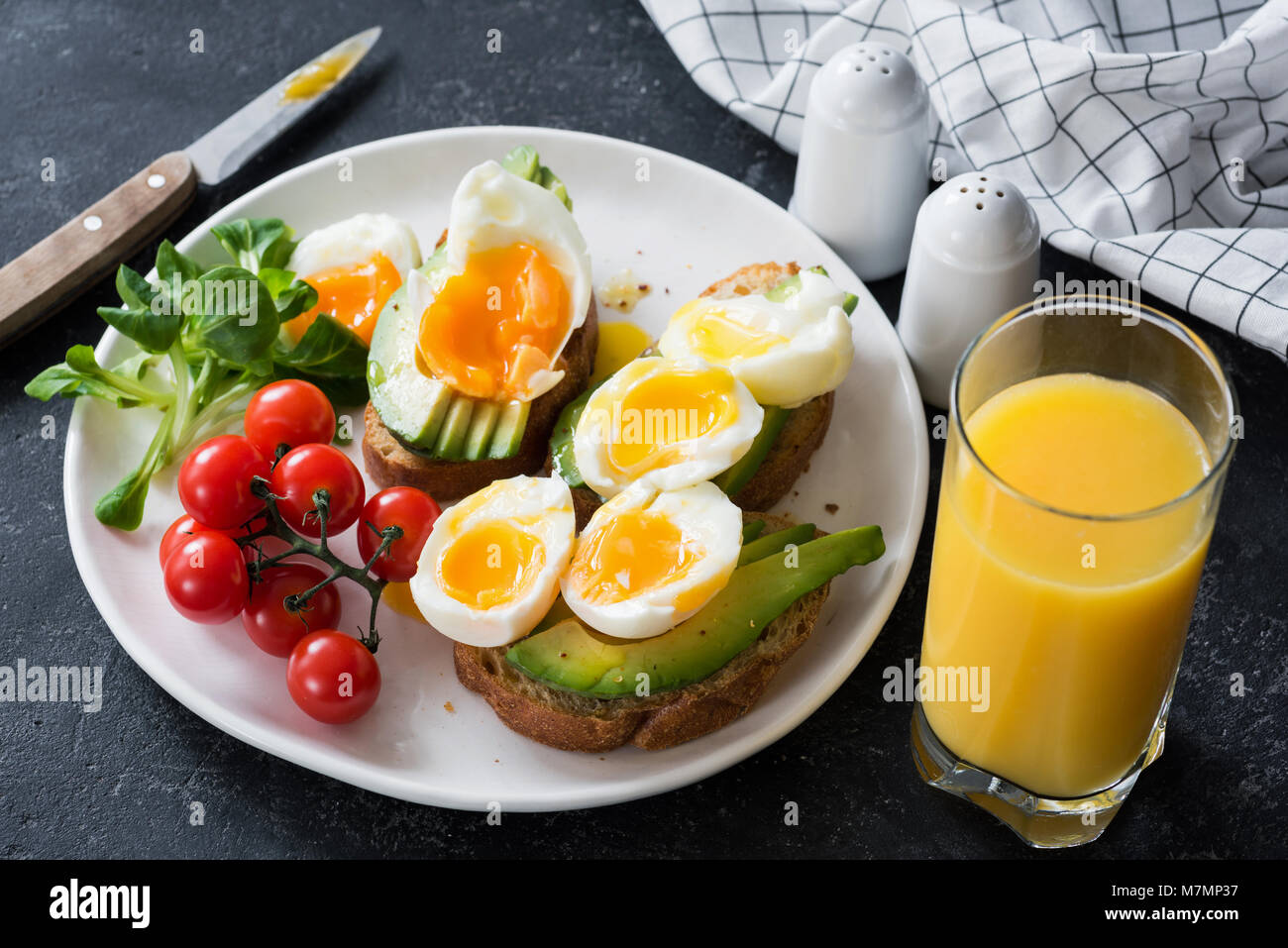 Avocado and poached egg toasts, salad and orange juice on stone table. Closeup view - Stock Image