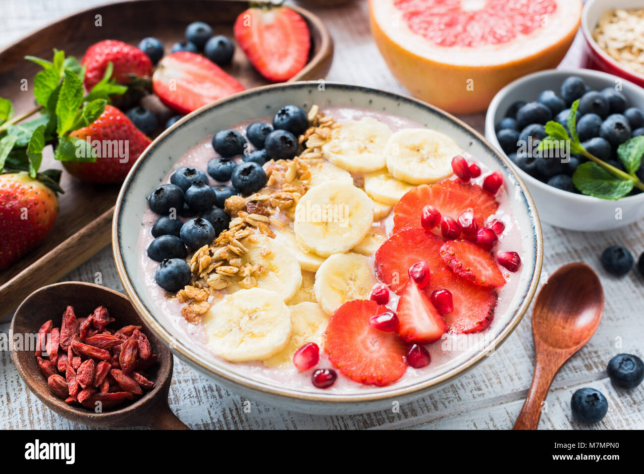 Smoothie bowl with strawberry, banana, blueberry, pomegranate and coconut flakes, closeup view. Concept of healthy - Stock Image