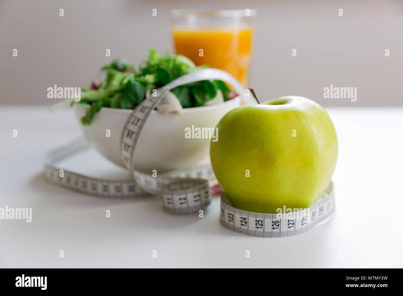 Measuring tape around the apple, bowl of green salad and glass of juice. Weight loss and right nutrition concept - Stock Image