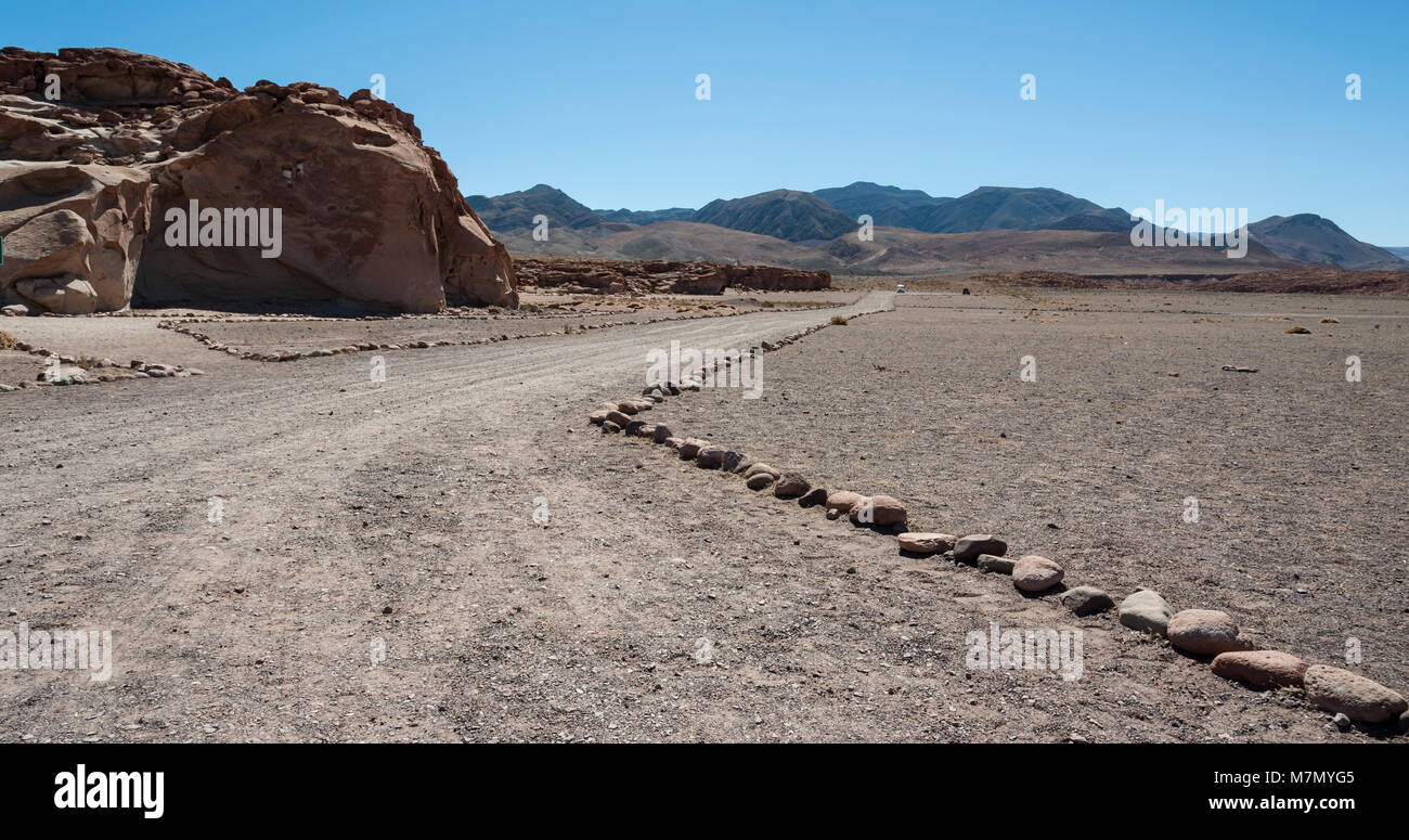 Unpaved road near Ancient Petroglyphs on the Rocks at Yerbas Buenas in Atacama Desert in Chile - Stock Image