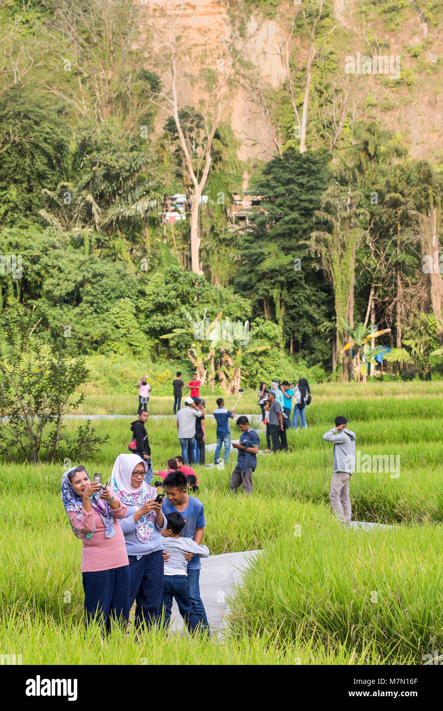 Groups of Local Indonesian friends and families enjoy a day out at a local attraction of a bendy concrete path leading - Stock Image