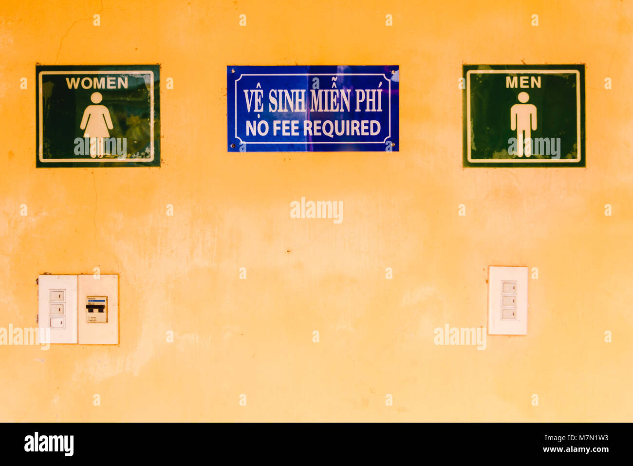 Signs at a public toilet advising that no fee is required to use them. - Stock Image